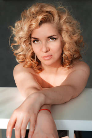 Beautiful spectacular 40 years old blonde with curly hair in a natural image with shoulders at a white table at home portrait large.