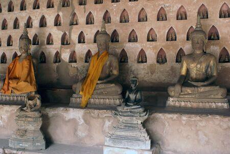 veneration: Buddhas and wall of buddhist wat, Laos