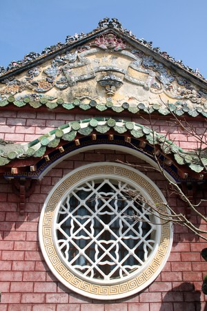 Circle window and wall of old vietnamise temple in Hoian, Vietnam photo