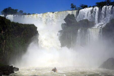 Red boat, mist and Iguazu falls in Argentina photo