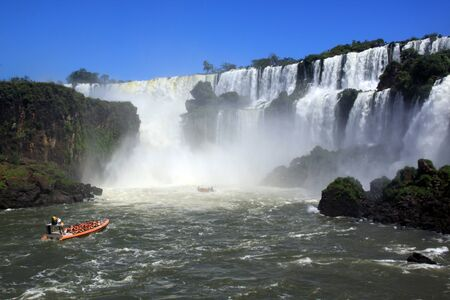 Two red boats and Iguazu waterfall in Argentina