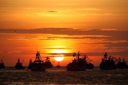 trawler: Fishing boats and sunset on the sea in Mancora, Peru Stock Photo