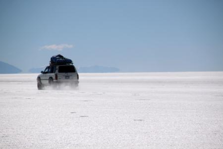 4 つの車輪ドライブ車とボリビアの塩の湖ウユニ 写真素材