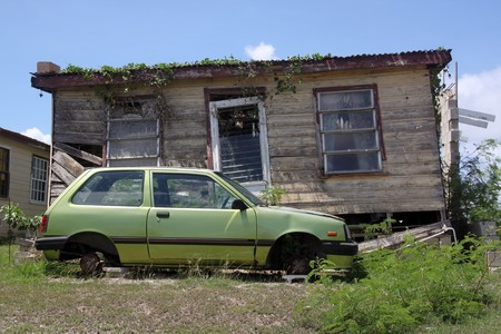 Old rusty house and green car withput wheels  photo
