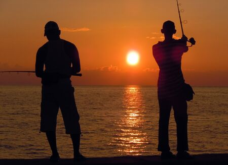 Fishing, people anmd sunset in Havana, Cuba