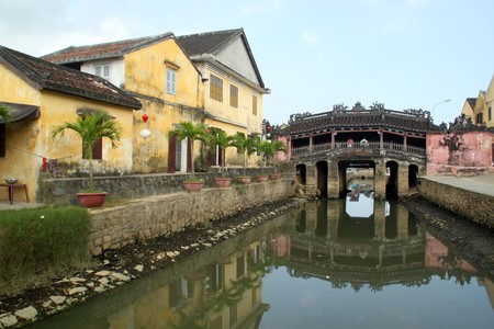 River, Yellow building and japanise bridge in Hoi An, Vietnam photo