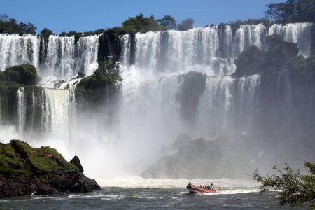 Wide Iguazu falls and red boat in Argentina photo
