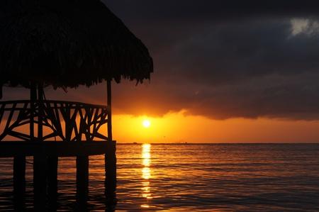 日没、クラウド、およびグアテマラのカリブ海岸の海の海岸の小屋 写真素材