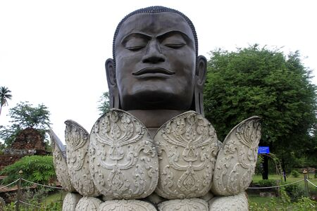 Big bronze head of Buddha and lotuses in Wat Thummikarat