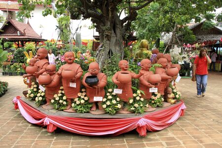 Ceramic statues of monks under tree in Wat Takarong in Ayutthaya, Thailand