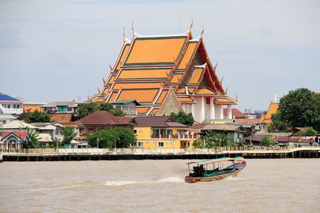 Boat and buddhist temple near WAt Srtun in Bangkok, Thailand