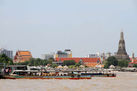 Long boat near the pier and view on Wat Arun in Bangkok, Thailand