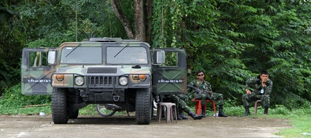 Soldiers wait near army jeep near the forest, Thailand