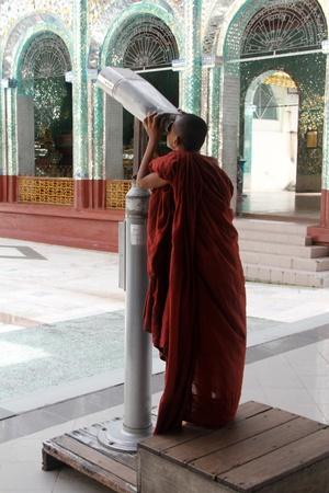 Monk tourist with telescope near Shwe Dagon paya pagoda in Yangon, Myanmar