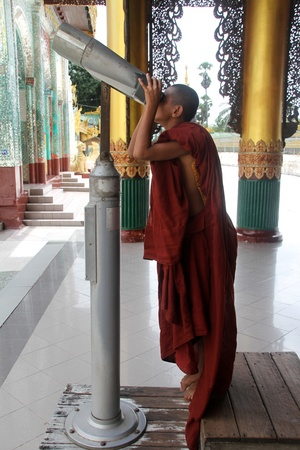 Monk tourist with telescope near Shwe Dagon paya pagoda in Yangon, Myanmar