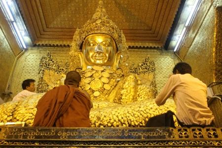 Men and monk near Mahamuni Buddha in Mandalay, Myanmar