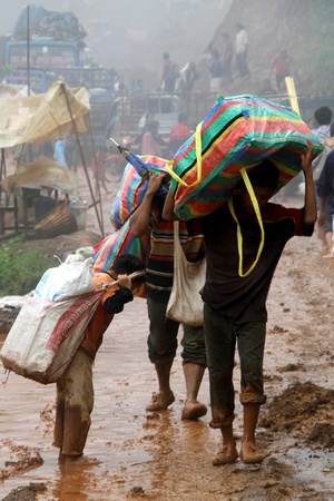 landslip: People carry heavy bags on the road after landslip, Laos Editorial
