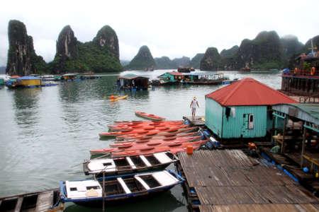 Kayaks on the water near wodden pier in Halong bay, Vietnam photo