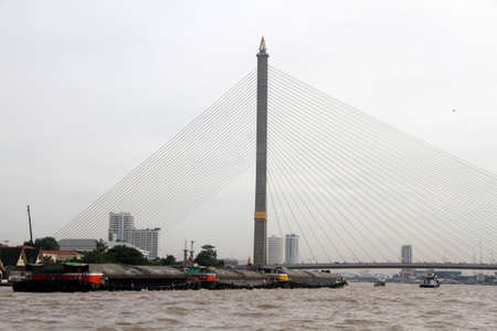 viii: New bridge and cargo barge on the Chao Phraya river in Bangkok, Thailand