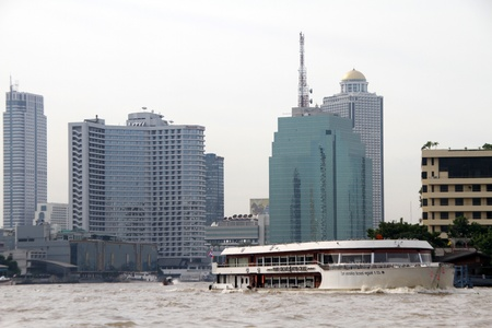 Buildings and ferry boat on the Chao Phraya river in Bangkok, Thailand