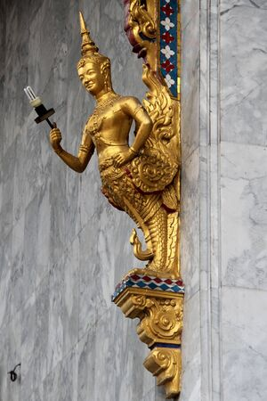 blissfull: Lamp and golden Buddha on the corner of marble wall of temple in wat Hualampong, Bangkok, Thailand