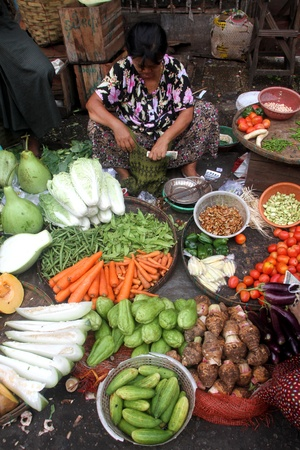 Woman with vegetables in the street market in Yangon, Myanmar