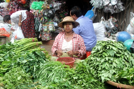 Vendor with raw greens on the stall in street msarket, Yangon, Myanmar