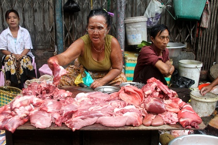 Vendor with raw meat on the stall in street msarket, Yangon, Myanmar