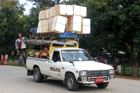 White pickup truck with heavy cargo on the road in Myanmar