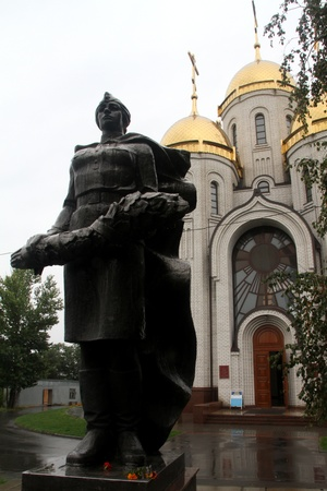 colden: Bronze russian soldier and orthodox church on Mamaev kurgan, Volgograd, Russia Stock Photo