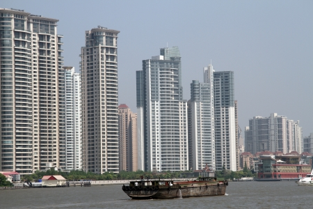 Cargo ship on the river Huangpu and new buildings in Shanghai, China