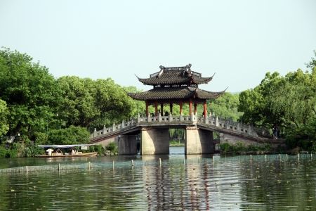 Bridge and tourist boat on the West lake in Hangzhou, China Stock Photo - 13852297