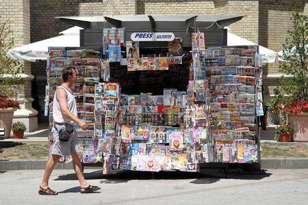新聞の売店とノヴィサド、セルビアで歩く人 報道画像