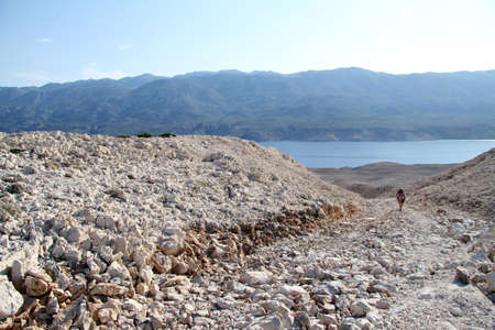 Backpacker on the footpath to the desert hill in Pag island, Croatia photo