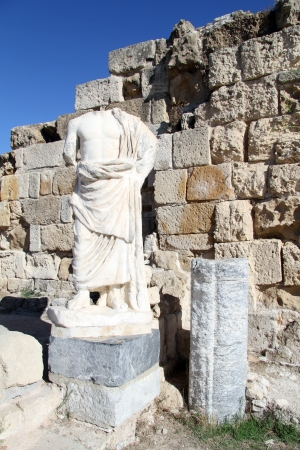 kibris: Headless statue near stone wall in Salamis, North Cyprus Stock Photo