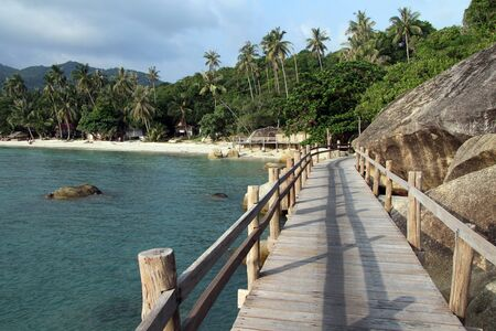 Sand beach and wooden path in Ko Phangan, Thailand photo