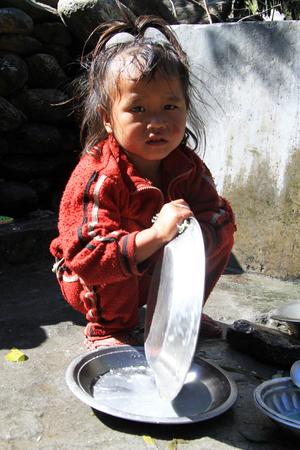 lavare piatti: JAGAT, NEPAL - CIRCA ottobre 2013 giovani lavare i piatti ragazza