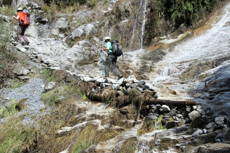 Two tourists on the rocky footpath near waterfall in mountain Nepal photo