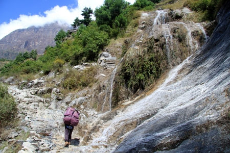 porter: Waterfall and porter in mountain in Nepal