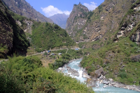 Dirt road a md mountain river on the Annapurna trail in Nepal photo