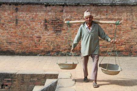 BHAKTAPUR, NEPAL - CIRCA NOVEMBER 2013 Man with yoke walk near the brick wall Editorial