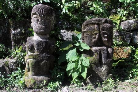 idols: Two stone idols near grave in Ambarita village, Indonesia