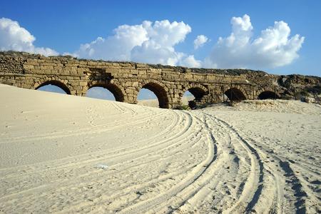 Tracks on the sand near aqueduct in Caesarea, Israel photo