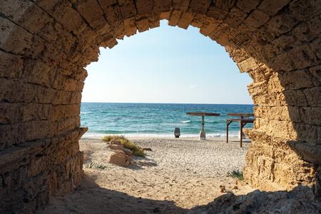 Entrance to the sand beach through the arch of aqueduct near Caesarea, Israekl photo