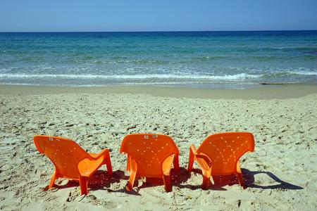 orange chairs: Orange plastic chairs on the sand beach near Netanya, Israel