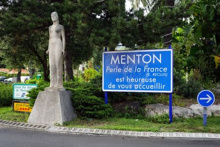 menton: MENTON, FRANCE - CIRCA JULY 2015 Statue and blue board on the street Editorial
