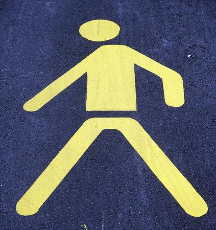 ideogram: Walking man yellow sign on asphalt road Stock Photo