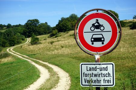 Road sign near track on the slope of hill in Germany