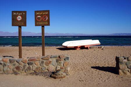 dahab: Boat and signs on the sand beach in Dahab, Egypt