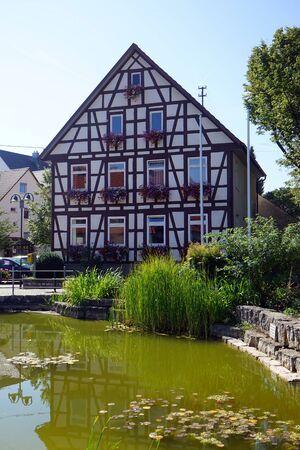 fachwerk: OCHSENWANG, GERMANY - CIRCA AUGUST 2015 Fachwerk house near green pond